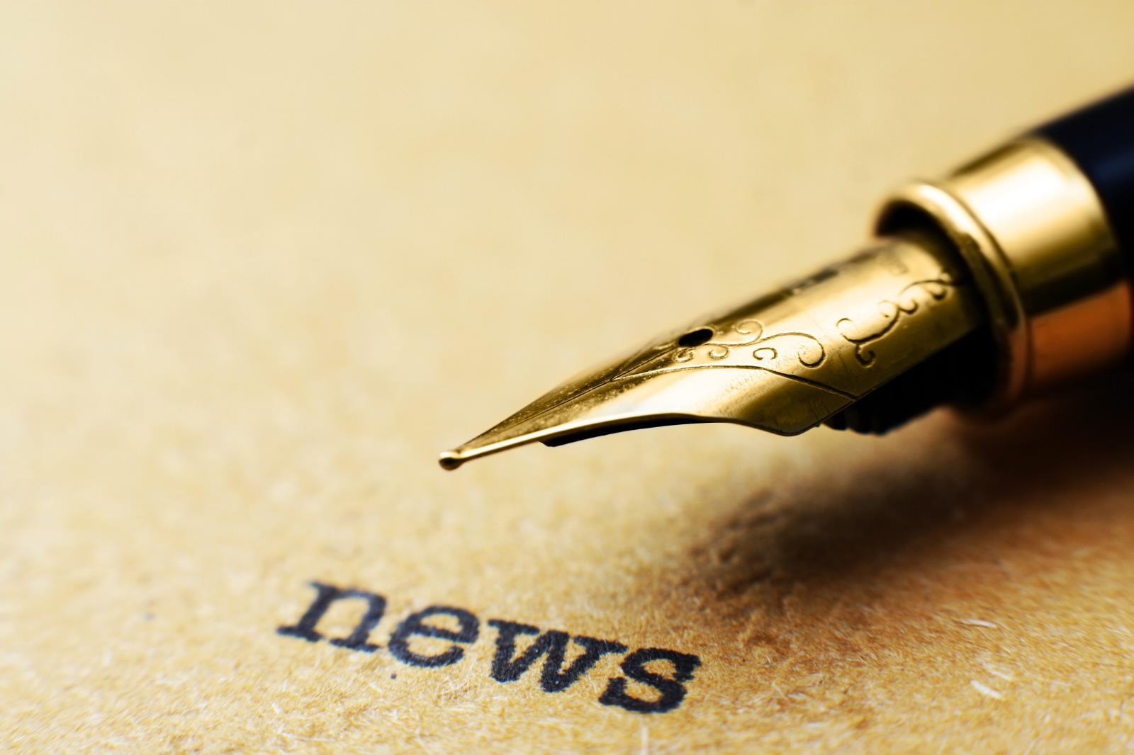 fountain-pen-on-news-text_MJdOgPDO