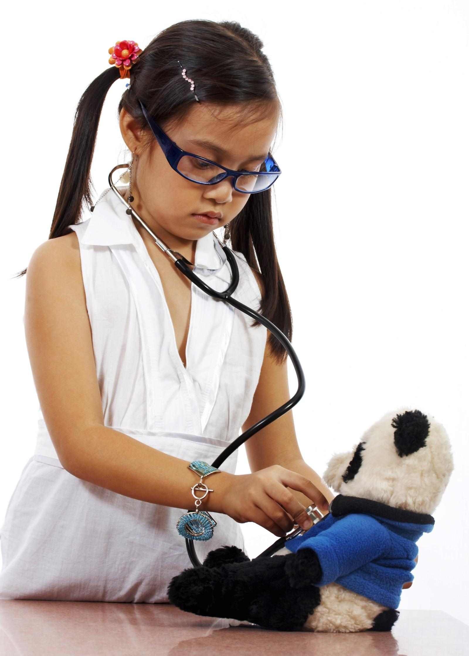 young child playing doctor with her teddy bear