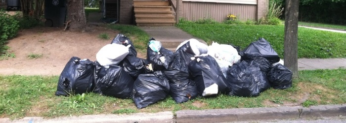 trash bags piled up in front of a house