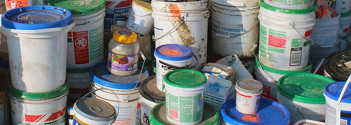 buckets of old paint stacked in a pile