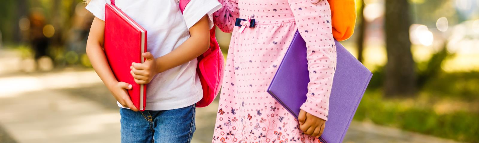 image of two young girls walking from or too school side by side