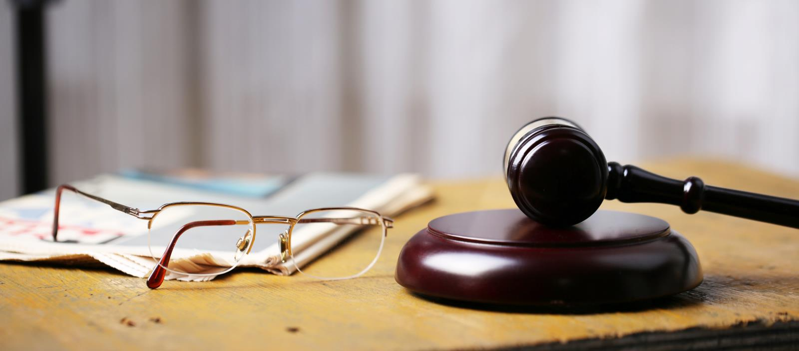 image of gavel book and eye glasses on a table