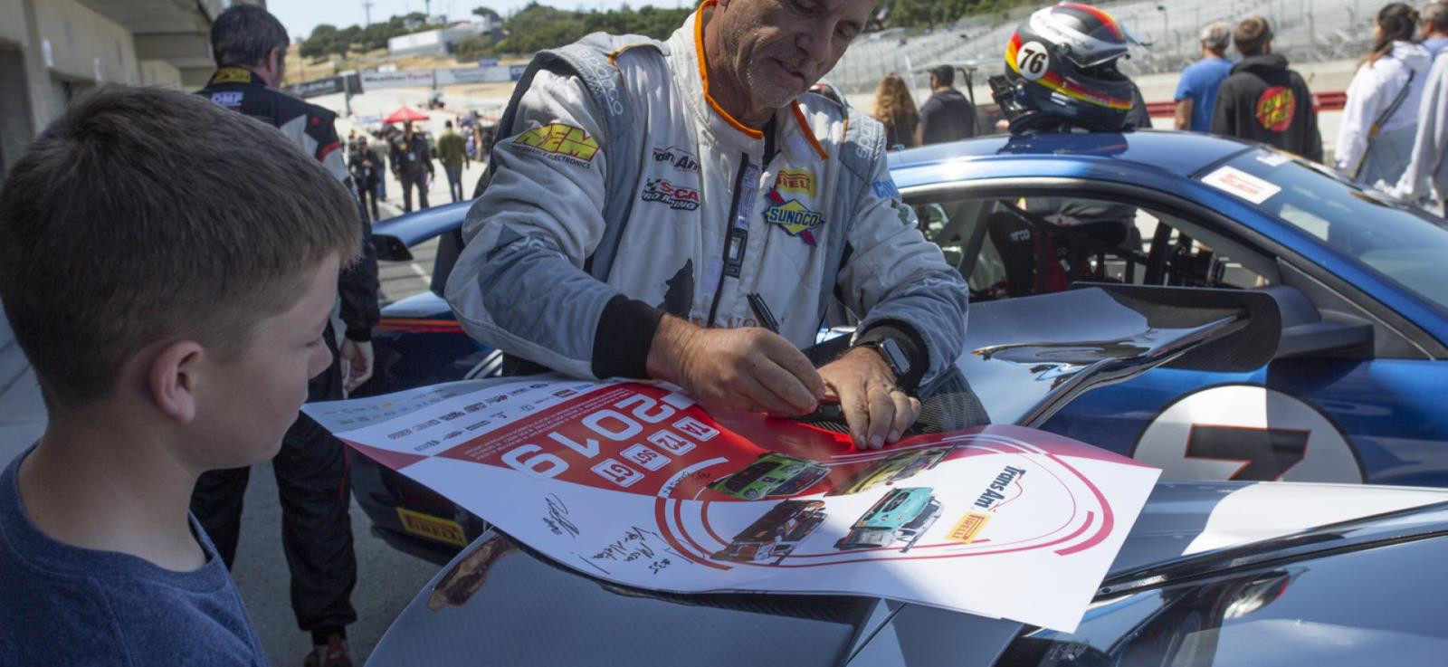 Photo of racer signing poster for adolescent
