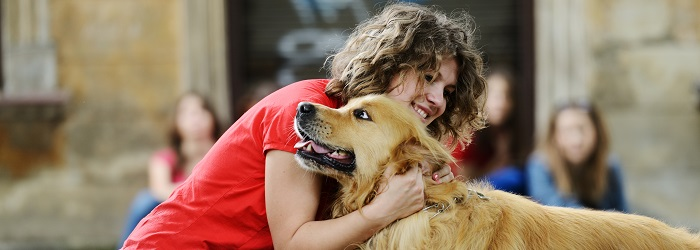 brown haired girl hugging a golden retriever